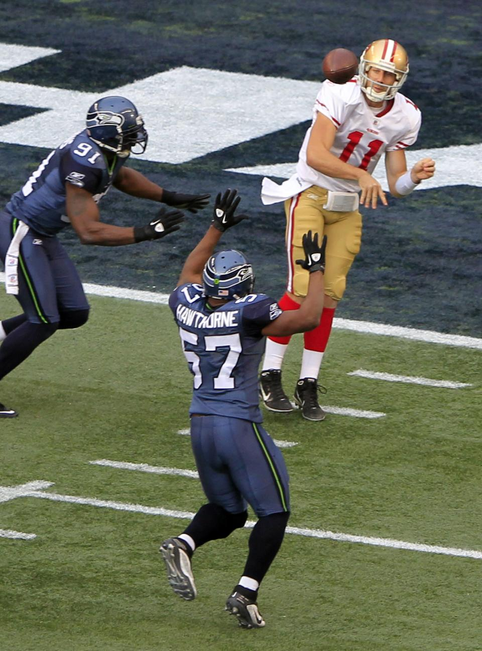 San Francisco 49ers quarterback Alex Smith (11) passes as Seattle Seahawks'  David Hawthorne (57) and Chris Clemons defending in the first half of an NFL football game in Seattle Saturday, Dec. 24, 2011. (AP Photo/John Froschauer)