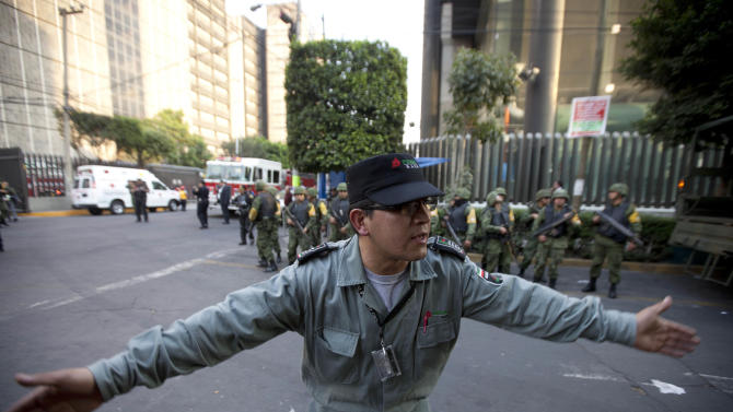 A worker belonging to Mexico's state-owned oil company PEMEX keeps journalists away after an explosion at an adjacent building to the executive tower of PEMEX in Mexico City, Thursday Jan. 31, 2013. An explosion at the main headquarters of Mexico's state-owned oil company in the capital Thursday left at least several workers injured, blew out windows and damaged the building, the company said. (AP Photo/Eduardo Verdugo)