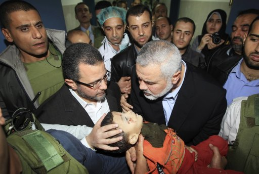 Senior Hamas leader Ismail Haniyeh and Egypt's Prime Minister Hisham Kandil touch the body of a Palestinian boy, who was killed in an Israeli air strike, during a visit to a hospital in Gaza City