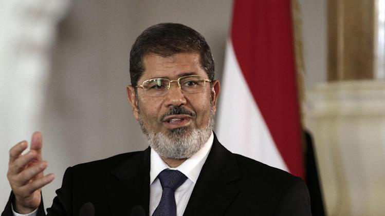 FILE - In this July 13, 2012 file photo, Egyptian President Mohammed Morsi speaks to reporters at the Presidential palace in Cairo. Egypt's streets have turned into a daily forum for airing a range of social discontents from labor conditions to fuel shortages and the casualties of myriad clashes over the past two years. Newly called parliamentary elections hold out little hope for plucking the country out of the turmoil and if anything, are likely to just fuel unrest and push it toward economic collapse. (AP Photo/Maya Alleruzzo, File)