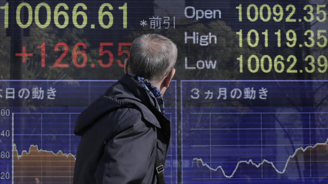 A man walks in front of the electronic stock board of a securities firm showing Japan's Nikkei 225 index that rose 126.55 points to 10,066.61 in Tokyo Tuesday, Dec. 25, 2012. Japan's benchmark stock index jumped Tuesday as a softening yen helped boost the country's powerhouse export sector. (AP Photo/Itsuo Inouye)