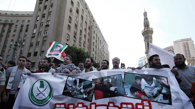 "Egyptian protesters hold a banner with Arabic that reads, ""save Gaza,"" during a protest in solidarity with Gaza after Israel launched its operation on Wednesday with the assassination of Hamas' top military commander in Cairo, Egypt, Thursday, Nov. 15, 2012. Egypt asked the United States to push Israel to stop its offensive against Hamas militants in the Gaza Strip, warning that the violence could ""escalate out of control,"" the Foreign Ministry said Thursday. (AP Photo/Ahmed Gomaa)"