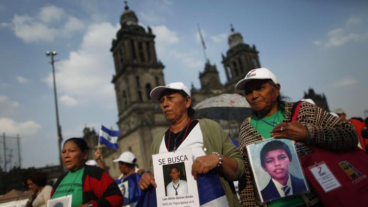 Women of the Caravan of Central American Mothers hold up photos of missing migrants during a march at Zocalo square in Mexico City