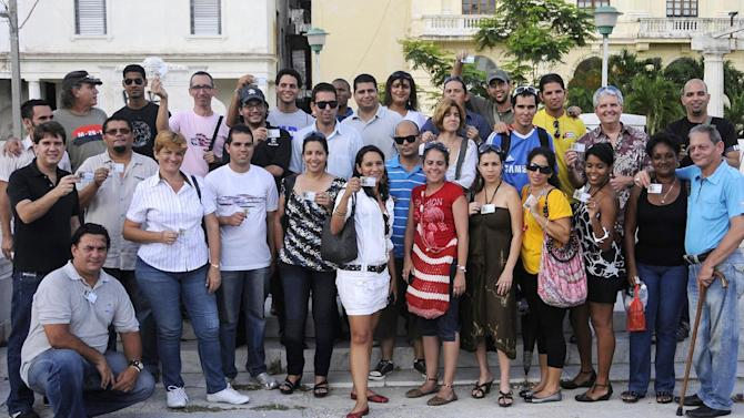 "In this May 10, 2013 photo, the No. 2 official at the U.S. Interests Section in Havana, Conrad Tribble, top row second from right, poses with Cuban bloggers and tweeters holding their name tags at the end of a meeting called TwittHab 2.0 in Havana, Cuba.  Dozens of young bloggers and tweeters gathered to talk about their place in a socialist society whose leaders have referred to the Internet as ""a wild colt"" to be tamed and make access difficult for all but a few. Tribble mostly listened for about an hour as others talked about things like the challenges of getting online in a country with the lowest Internet connectivity rate in the Western Hemisphere. (AP Photo/Roberto Suarez)"