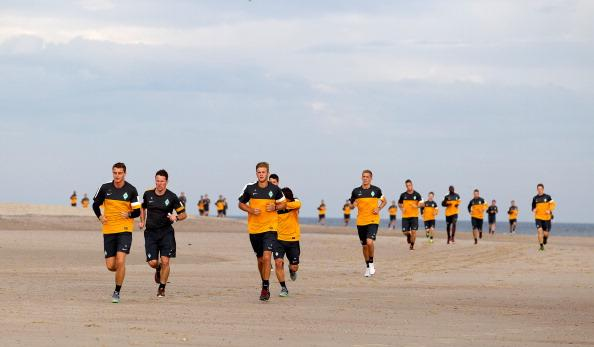 Players of Werder Bremen run on the beach during a SV Werder Bremen training session on July 8, 2012 in Norderney, Germany. (Photo by Martin Stoever/Bongarts/Getty Images)