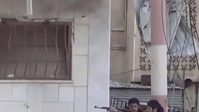 In this image taken from video obtained from the Shaam News Network, which has been authenticated based on its contents and other AP reporting, Free Syrian Army figthers fire at Syrian army soldiers during a fierce firefight in Daraa al-Balad, Syria, Monday March 18, 2013. Two years after the anti-Assad uprising began, the conflict has become a civil war, with hundreds of rebel group fighting Assad's forces across Syria and millions of people pushed from their homes by the violence. The U.N. says more than 70,000 people have been killed. (AP Photo/Shaam News Network via AP video)