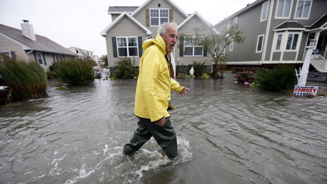 Richard Thomas walks through the flood waters in front of his home after assisting neighbors as Hurricane Sandy bears down on the East Coast, Monday, Oct. 29, 2012, in Fenwick Island, Del. Forecasters warned that the New York City region could face the worst of Hurricane Sandy as it bore down on the U.S. East Coast's largest cities Monday, forcing the shutdown of financial markets and mass transit, sending coastal residents fleeing and threatening high winds, rain and a wall of water up to 11 feet (3.35 meters) tall. It could endanger up to 50 million people for days.  (AP Photo/Alex Brandon)