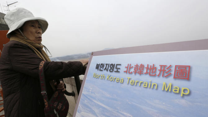 """A visitor looks at North Korean territory at the unification observation post near the border village of Panmunjom, that has separated the two Koreas since the Korean War, in Paju, north of Seoul, South Korea, Saturday, March 30, 2013. North Korea issued its latest belligerent threat Saturday, saying it has entered """"a state of war"""" with South Korea a day after its young leader threatened the United States because two American B-2 bombers flew a training mission in South Korea. (AP Photo/Lee Jin-man)"""