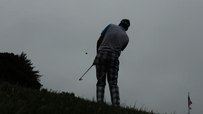 Ian Poulter, of England, practices chipping as he waits out a weather delay during the first round of the U.S. Open golf tournament at Merion Golf Club, Thursday, June 13, 2013, in Ardmore, Pa. (AP Photo/Charlie Riedel)
