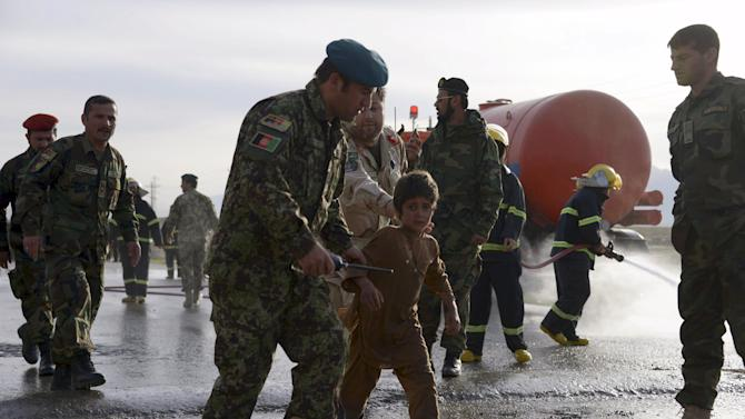 An Afghan National Army officer escorts a slightly injured boy from the site of a suicide attack on the outskirts of Mazar-i-Sharif, Afghanistan