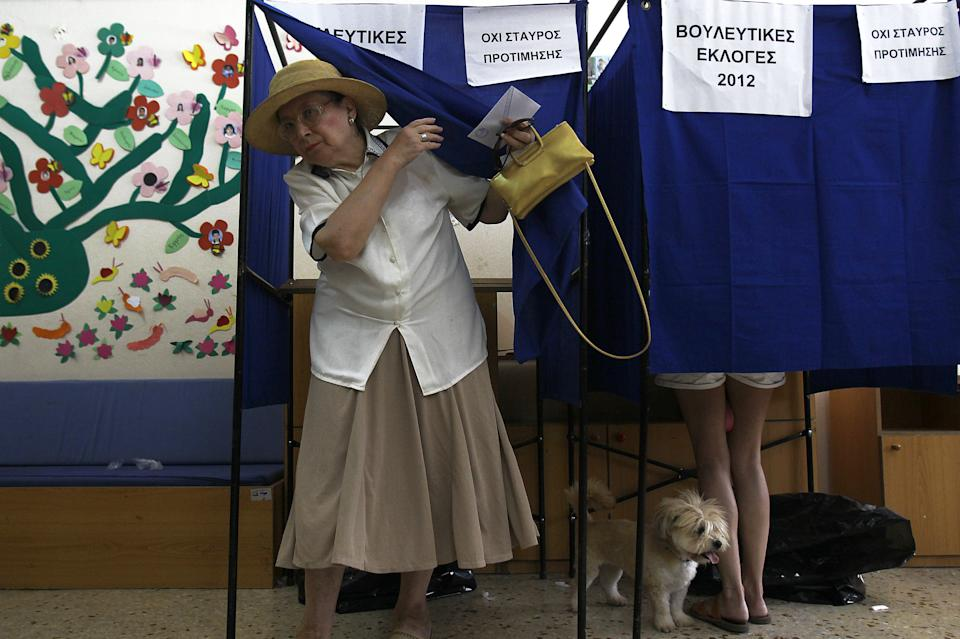 A Greek woman leaves the booth after voting during the parliamentary elections in Athens, Sunday, June 17, 2012.  The sign reads in Greek Parliamentary elections 2012. The signs reads: Parliamentary elections 2012. (AP Photo/Petros Karadjias)