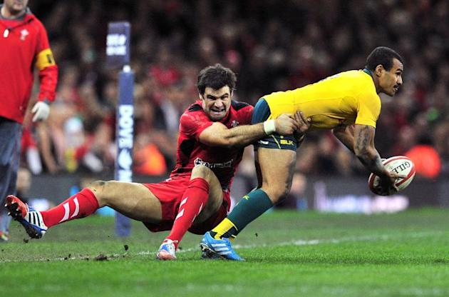Wales' scrum-half Mike Phillips (L) tackles Australia's Will Genia during their rugby union Test match, at the Millennium Stadium in Cardiff, Wales, on November 30, 2013