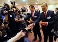 Ronald Arculli (R), former head of the Hong Kong Stock Exchange, hands out 'Lai See' or lucky money to journalists on the first trading day of the Year of the Rabbit in Hong Kong on February 7. He retired after six years in the position