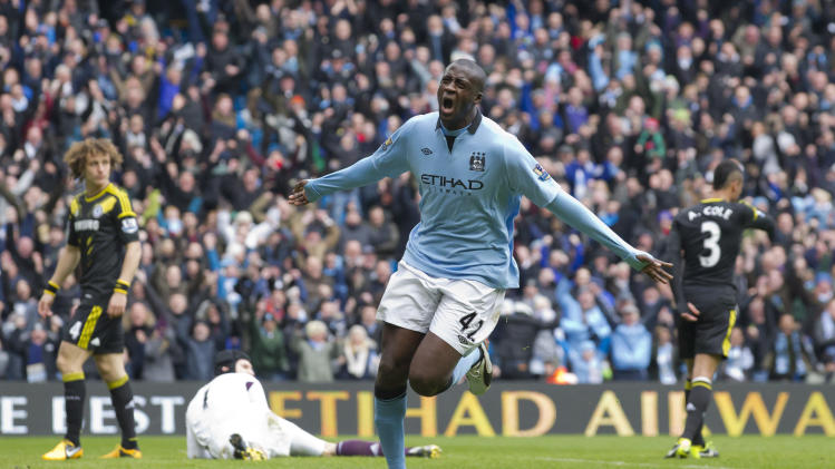 Manchester City's Yaya Toure, centre, celebrates after scoring against Chelsea during their English Premier League soccer match at The Etihad Stadium, Manchester, England, Sunday Feb. 24, 2013. (AP Photo/Jon Super)