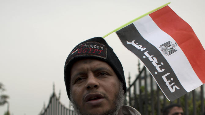 "A man wears a T-shirt with the portrait of Egyptian President Mohammed Morsi with a national flag attached to his beanie with Arabic that reads, ""we all love Egypt,"" in front of Egypt's top court in Cairo, Egypt, Sunday, Dec. 2, 2012. Egypt's top court announced on Sunday the suspension of its work indefinitely to protest ""psychological and physical pressures,"" saying its judges could not enter its Nile-side building because of the Islamist president's supporters gathered outside. (AP Photo/Nasser Nasser)"