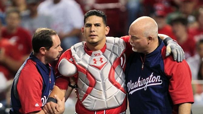 Washington Nationals catcher Wilson Ramos, center, is helped off the field after being injured in the seventh inning of a baseball game against the Cincinnati Reds, Saturday, May 12, 2012, in Cincinnati. Washington won 2-1. (AP Photo/Al Behrman)