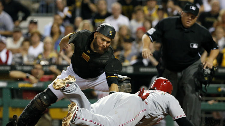 Pittsburgh Pirates catcher Russell Martin prepares to make the sweep tag on Cincinnati Reds' Brandon Phillips for the final out of the eighth inning during a baseball game in Pittsburgh Friday, Aug. 29, 2014. Phillips was attempting to score on a double by Reds' Devin Mesoraco. (AP Photo/Gene J. Puskar)