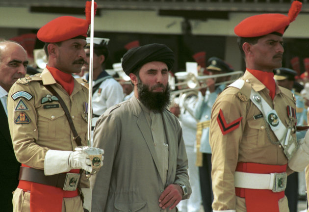 FILE - In this Wednesday, June 26, 1996 file photo, Gulbuddin Hekmatyar, center, passes in front of an honor guard in the Afghan capital of Kabul, Afghanistan, after being sworn in as prime minister, ending four years of bitter fighting among U.S. backed rebels who took control of Kabul from the communist regime. Hekmatyar today is a U.S.-declared terrorist in hiding fighting international forces in Afghanistan. His representatives have opened talks with President Hamid Karzai's political opponents, as well as Karzai. (AP Photo, File)