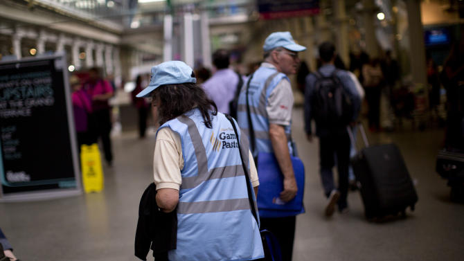 """Volunteer pastors Douglas and Magarita Barr-Hamilton roam the St. Pancras station as they look for people to help on Wednesday, Aug. 8, 2012, in London. Roaming London's transport network in blue baseball caps are 300 volunteer """"games pastors"""" from a range of Christian denominations. Deployed at airports and train stations, they are ready to step into the most trivial or most serious situation, from a lost contact lens to a potential suicide. (AP Photo/Emilio Morenatti)"""