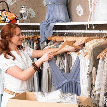 Young-woman-in-clothes-shop-hanging-dress-on-hanger_web