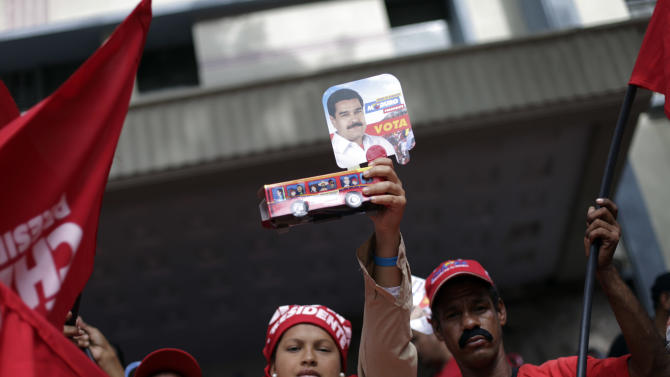 A supporter of Venezuela's President-elect Nicolas Maduro, holds up an image of Maduro and a cardboard bus, outside the parliament building prior to his inauguration ceremony in Caracas, Venezuela, Friday, April 19, 2013. Opponents greeted officials' surprise announcement that they will accept an audit of the disputed vote that handed a narrow margin of victory to Maduro, a former bus driver who rose up through the ranks of Chavismo, becoming the heir of late President Hugo Chavez. (AP Photo/Ramon Espinosa)