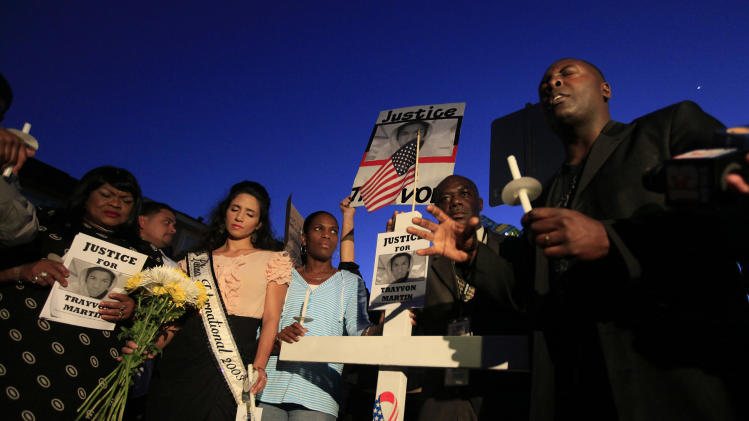 Marc Booker, of Sanford, leads a prayer during the candlelight vigil at the memorial site outside the gates of the Retreat at Twin Lakes, where Trayvon Martin was shot by neighborhood watch captain George Zimmerman, in Sanford, Fla., Sunday, March 25, 2012.  (AP Photo/Julie Fletcher)