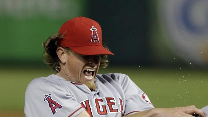 Los Angeles Angels starting pitcher Jered Weaver reacts to getting hit in the arm with a line drive during the sixth inning of a baseball game against the Texas Rangers Sunday, April 7, 2013, in Arlington, Texas.  Weaver left the game. (AP Photo/LM Otero)