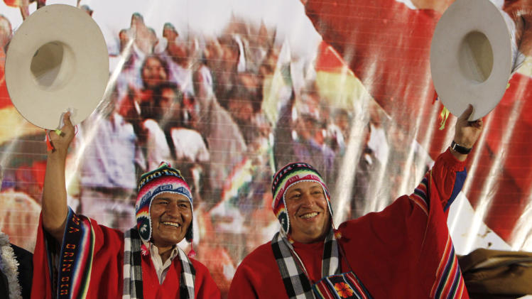 FILE - In this March 31, 2011 file photo, Venezuela's President Hugo Chavez, right, and Bolivia's President Evo Morales, dressed in traditional Quechua indigenous clothing, wave to supporters at a welcoming ceremony for Chavez in Cochabamba, Bolivia. Venezuela's Vice President Nicolas Maduro announced on Tuesday, March 5, 2013 that Chavez has died.  Chavez, 58, was first diagnosed with cancer in June 2011. (AP Photo/Juan Karita, File)
