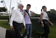 Formula One Chief Executive Bernie Ecclestone (L) and his wife Fabiana Flosi (R) walk with an unidentified man ahead of the third practice session of the Singapore F1 Grand Prix at the Marina Bay street circuit in Singapore September 21, 2013. REUTERS/Pablo Sanchez