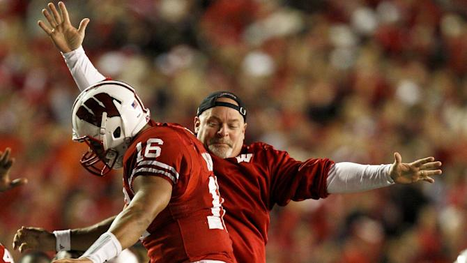 Wisconsin's Russell Wilson (16) celebrates with a Wisconsin staff member after a Wisconsin touchdown against Nebraska during the first half of an NCAA college football game Saturday, Oct. 1, 2011, in Madison, Wis. (AP Photo/Andy Manis)