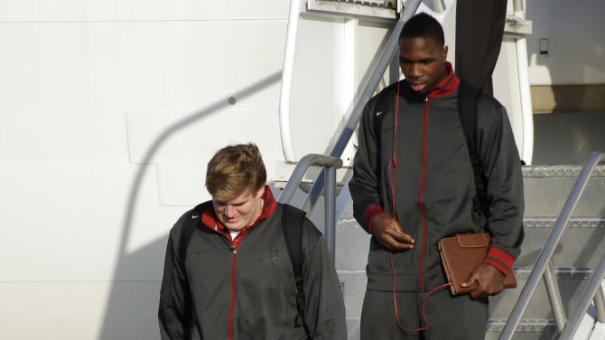 Alabama offensive lineman Barrett Jones, foreground, walks off the team plane upon arrival at Miami International Airport, Wednesday, Jan. 2, 2013, in Miami. Jones sprained his left foot during the first quarter of the Southeastern Conference championship game against Georgia on Dec. 1. Alabama is scheduled to play Notre Dame in the BCS national championship NCAA college football game next Monday in Miami. (AP Photo/Wilfredo Lee)