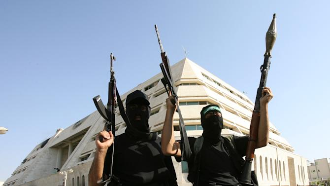 Hamas fighters tot their arms as they stand in front of the pro-Fatah Palestinian Intelligence Security compound in Gaza City, 14 June 2007