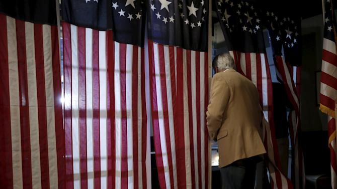 A voter enters a voting booth to fill out a ballot in the U.S. Presidential primary election at the Hale House at Balsams Hotel in Dixville Notch