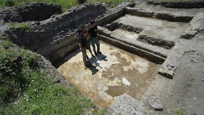 Darius Arya (L), in charge of the excavation for the American Institute for Roman Culture, presents a marble floor as part of the last discoveries at the Parco dei Ravennati excavation site in Ostia Antica on July 17, 2014