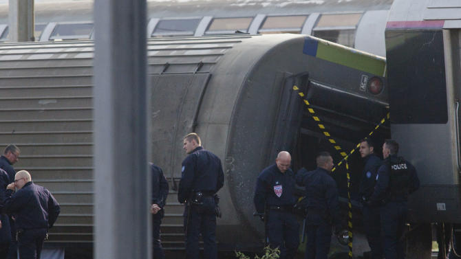 Police officers investigate on the site where a train derailed at a station in Bretigny sur Orge, south of Paris, Saturday, July 13, 2013. France's transport minister says human error did not cause a train derailment outside Paris that left six dead. Frederic Cuvillier said Saturday that around 30 people were still considered injured. In all, nearly 200 people sustained injuries in the initial accident, when four train cars slid toward the station, some falling over. (AP Photo/Thibault Camus)