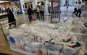 Emiratis and foreigners pass next to donation boxes …