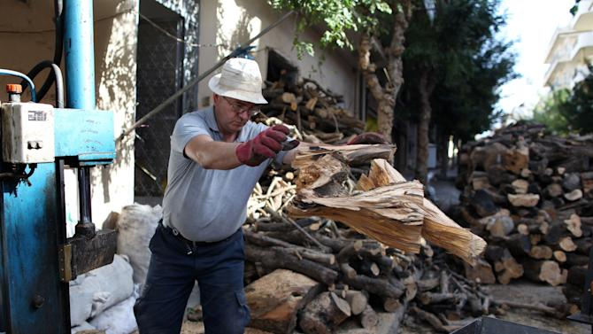 In this picture taken on Oct. 16, 2012 , Costas Tsakoyiannis splits logs in his firewood yard near a central Athens cemetery. A steep increase in heating costs has forced many in crisis-hit Greece to switch from heating oil to wood-burning for warmth. But there's a catch. Illegal loggers are slashing through forests devastated by years of summer wildfires, air pollution from wood smoke is choking the country's main cities and there has been an increase in blazes caused by carelessly attended woodstoves.(AP Photo/Petros Giannakouris)