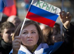 A woman holds a Russian flag with the word reading …