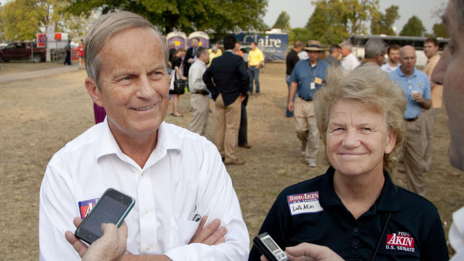 In this Thursday, Aug. 16, 2012 photograph, Rep. Todd Akin, R-Mo., and his wife Lulli, talk with reporters while attending the Governor's Ham Breakfast at the Missouri State Fair in Sedalia, Mo. Akin was keeping a low profile, Monday, Aug. 20, 2012, a day after a TV interview in which he said that women's bodies can prevent pregnancies in