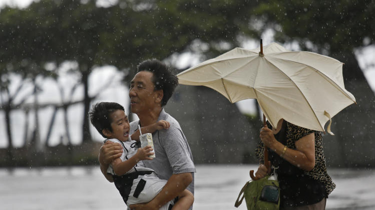 A family from Mainland China battle against strong wind near the waterfront in Hong Kong Wednesday, Aug. 14, 2013. Typhoon Utor lashed Hong Kong with wind and rain, closing down the bustling Asian financial center Wednesday before sweeping toward mainland China. (AP Photo/Vincent Yu)