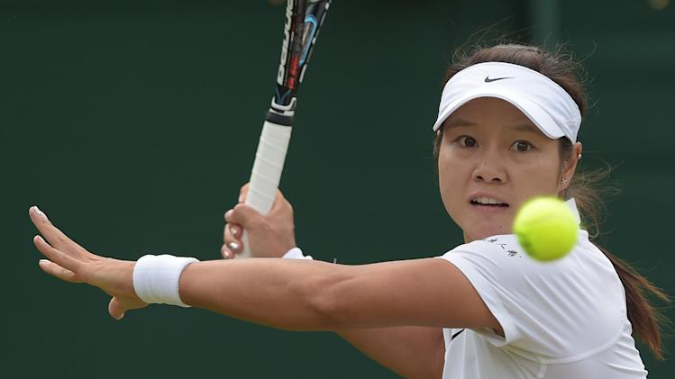 China's Li Na hits a return to Austria's Yvonne Meusburger (unseen) during their women's singles match during the Wimbledon Championships in southwest London, on June 25, 2014