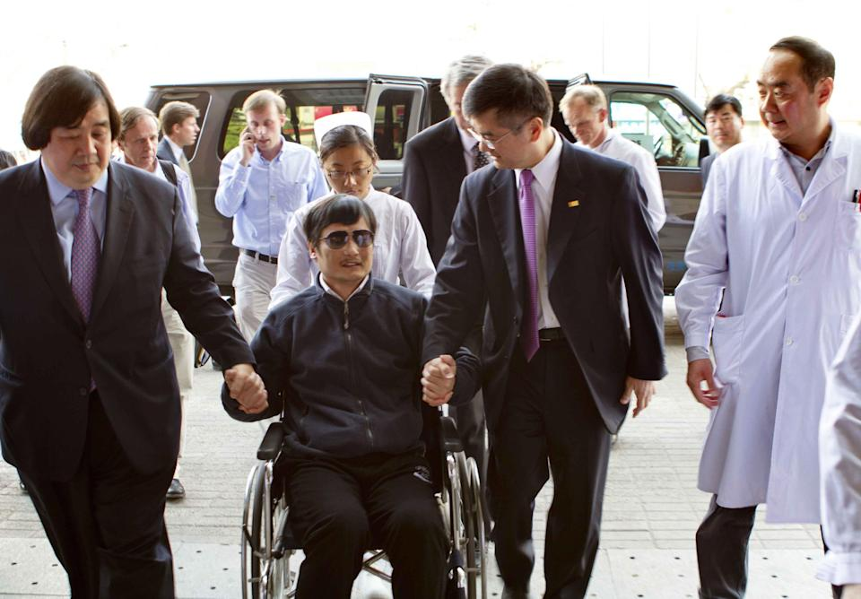 In this photo released by the US Embassy Beijing Press Office, blind lawyer Chen Guangcheng is wheeled into a hospital by U.S. Ambassador to China Gary Locke, right, and an unidentified official at left, in Beijing Wednesday May 2, 2012. (AP Photo/US Embassy Beijing Press Office, HO)
