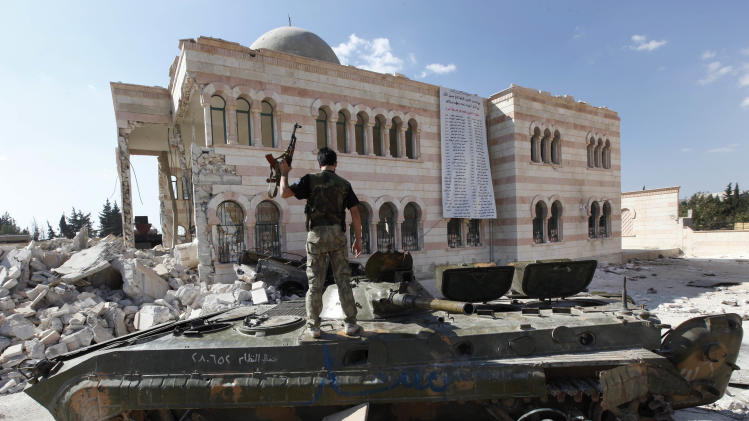 A Free Syrian Army soldier stands on a damaged Syrian military tank in front of a damaged mosque, which were destroyed during fighting with government forces, in the Syrian town of Azaz, on the outskirts of Aleppo, Sunday, Sept. 23, 2012. Syria's bloody 18-month conflict, which activists say has killed nearly 30,000 people, has so far eluded all attempts at international mediation.(AP Photo/Hussein Malla)