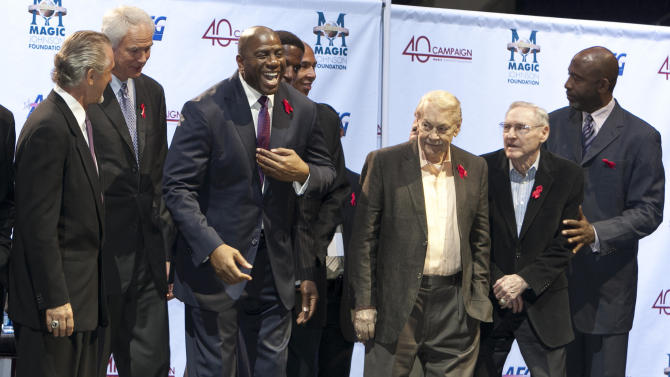 FILE - In this Nov. 7, 2011 file photo, Los Angeles Lakers owner Jerry Buss, third from right, looks towards Magic Johnson, third from left, during a ceremony of the Magic Johnson Foundation in Los Angeles. Also shown are former Lakers team members Pat Riley, left, Mitch Kupchak, second from left, Bill Sharman, second from right, and James Worthy, right. Buss, the Lakers' playboy owner who shepherded the NBA franchise to 10 championships, has died. He was 79. Bob Steiner, an assistant to Buss, confirmed Monday, Feb. 18, 2013  that Buss had died in Los Angeles. Further details were not available.(AP Photo/Damian Dovarganes, FIle)