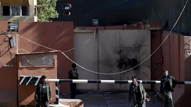 Afghan security force stand at the gate of a guesthouse after an attack in Kabul
