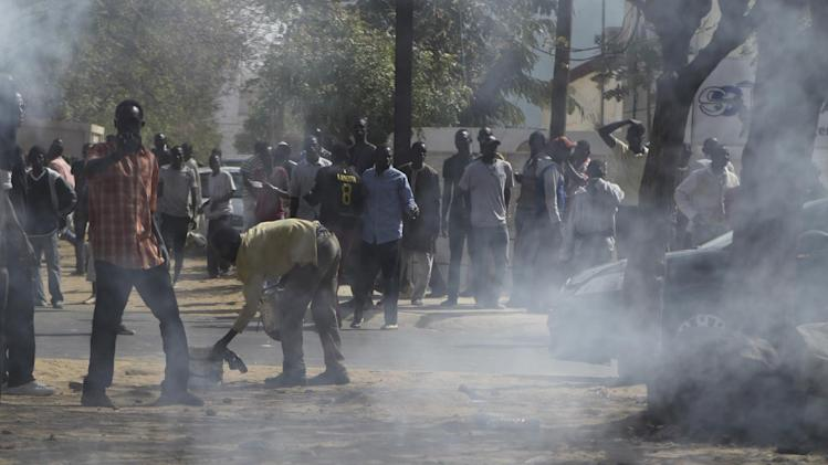 Supporters of President Abdoulaye Wade retreat from tear gas, fired by security forces, outside the polling station where Wade was due to vote, in the Point E neighborhood of Dakar, Senegal Sunday, March 25, 2012. Senegalese voters are deciding Sunday whether to give their 85-year-old president another term in office, or instead back his one-time protege Macky Sall in a runoff election that could oust the incumbent of 12 years. (AP Photo/Rebecca Blackwell)