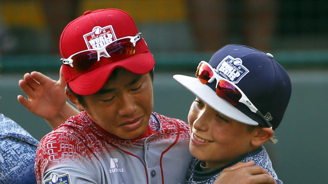 Lewisberry, Pa.'s Bailey Wirt (9) hugs Japan's Yugo Aoki after the Little League World Series Championship baseball game in South Williamsport, Pa., Sunday, Aug. 30, 2015. Japan won 18-11. (AP Photo/Gene J. Puskar)