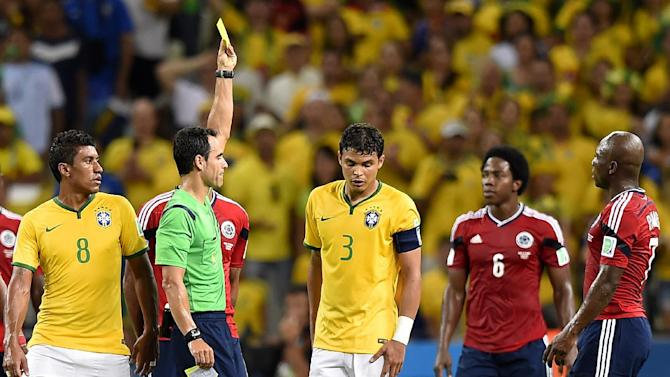 Carlos Velasco (2nd left) gives a yellow card to Brazil captain Thiago Silva (centre) during the quarter-final against Colombia in Fortaleza on July 4, 2014