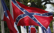 "Confederate battle flags fly outside the museum at the Confederate Memorial Park in Mountain Creek, Ala., Tuesday, July 19, 2011. More than 60,000 Confederate veterans came home to Alabama after the Civil War, and residents are still paying a tax that supported them 150 years after the fighting began. The tax now pays for the park, which is located on the same 102-acre tract where elderly veterans used to stroll. The tax once brought in millions for Confederate pensions, but lawmakers sliced up the levy and sent money elsewhere as the men and their wives died. No one has seriously challenged the continued use of the money for a memorial to the ""Lost Cause,"" although a long-serving black legislator wants to eliminate state funding for the park. (AP Photo/Dave Martin)"