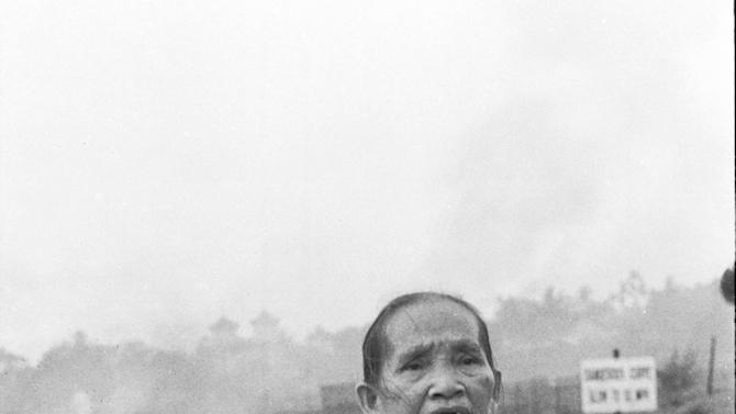 """FILE - In this June 8, 1972 file photo taken by Associated Press photographer Huynh Cong """"Nick"""" Ut, a Vietnamese grandmother carries her severely burned one-year-old grandson down Route 1 after a misdirected napalm attack by South Vietnamese pilots in the village of Trang Bang, South Vietnam. The napalm attack was intended for enemy forces on the outskirts of the village. It only took a second for Ut to snap the iconic black-and-white image of another victim of the attack, Phan Thi Kim Phuc, but it communicated the horrors of the Vietnam War in a way words could never describe, helping to end one of America's darkest eras. (AP Photo/Nick Ut, File)"""